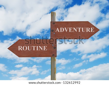 wooden crossroad sign on cloudy background with adventure vs routine  writing - stock photo