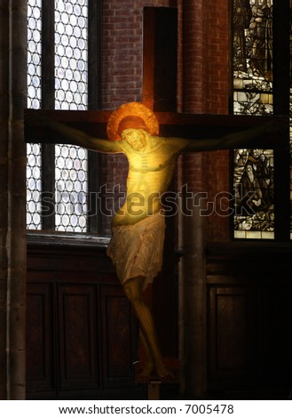 Wooden crucifix lit by a spotlight in the Santa Maria Gloriosa dei Frari church in Venice, Italy. - stock photo
