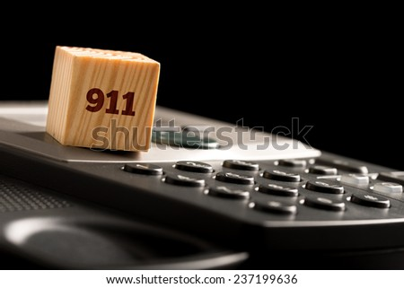 Wooden cube with 911 on a phone keyboard conceptual of emergency call over a dark background with copyspace. - stock photo