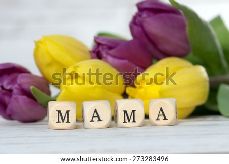 Wooden cube with tulips and the word Mama / Mama - stock photo