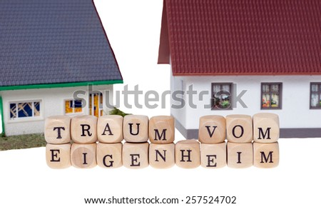 Wooden cubes and the german words dream of home ownership / home ownership - stock photo