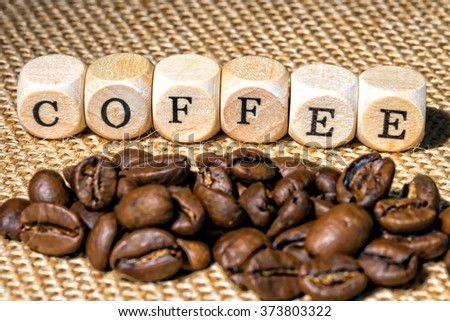 wooden cubes with the word Coffee and Coffee beans lying on jute fabric / Coffee beans - stock photo
