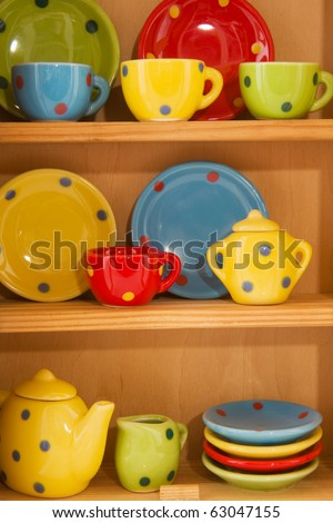 wooden cupboard with cheerful crockery with dotts - stock photo