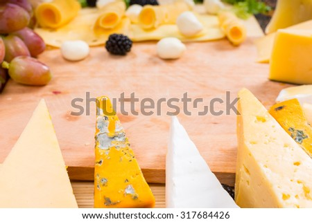 Wooden Cutting Board Surrounded by Variety of Gourmet Cheese Wedges and Fresh Fruit with Copy Space in Center of Image - stock photo