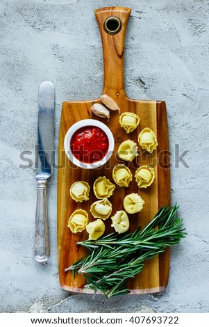 Wooden cutting board with homemade raw Italian tortellini, tomato sauce and rosemary over concrete textured background, border, top view. - stock photo