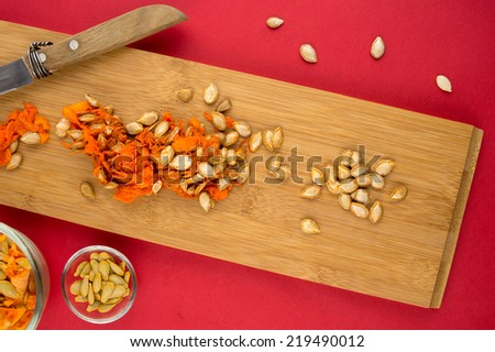 Wooden cutting board with orange squash seeds against red background - stock photo