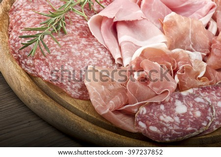 Wooden cutting board with various Italian salami  - stock photo