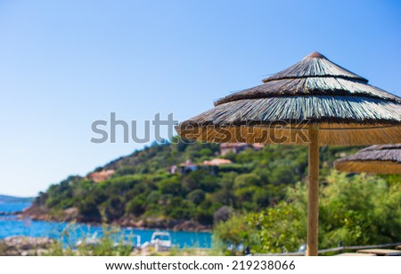 Wooden deck chairs and umbrellas near infinity pool in luxury resort - stock photo