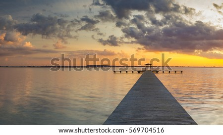 wooden deck overlooking the lake, the beautiful evening sky, colored by the setting sun