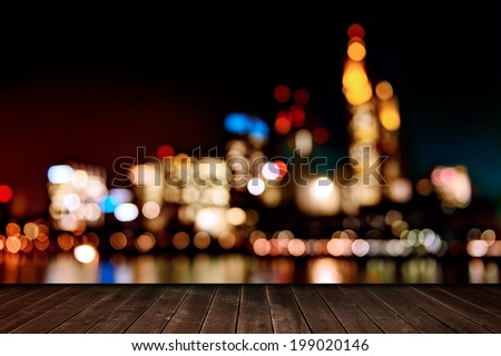 wooden deck table anddefocused night lights of the Frankfurt am Main, Germany - stock photo