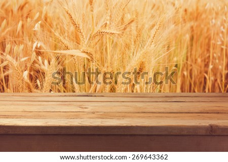 Wooden deck table over wheat field background - stock photo
