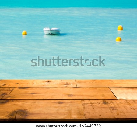 Wooden decking or picnic table on St Martin in Caribbean in idyllic dreamlike location with a powerboat moored just off the harbor in the turquoise ocean - stock photo