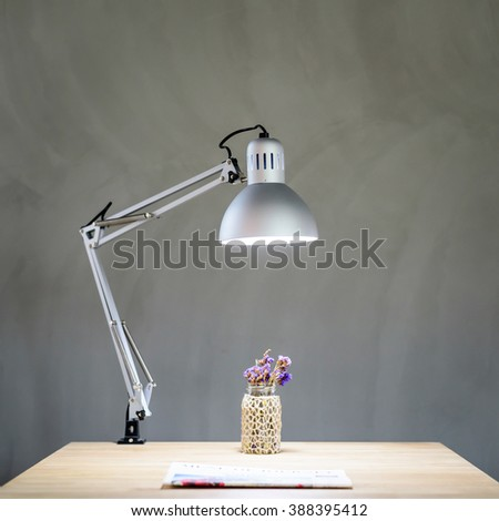 Wooden Desk with Lamp in front of concrete wall in modern office - stock photo