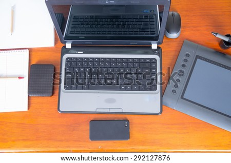 Wooden desk with open laptop next to cell phone, digital drawing board and external harddrive shot from above angle - stock photo