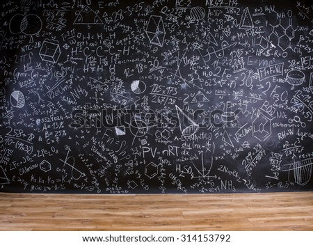Wooden desk with school supplies in front of big blackboard - stock photo