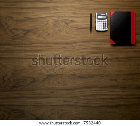 wooden desktop with calculator pen and book - stock photo
