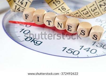 Wooden dice with the word Fitness and a body scale / Fitness - stock photo