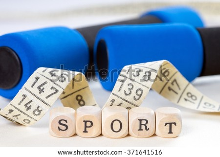 Wooden dice with the word sport and tape measure with dumbbells / Sport