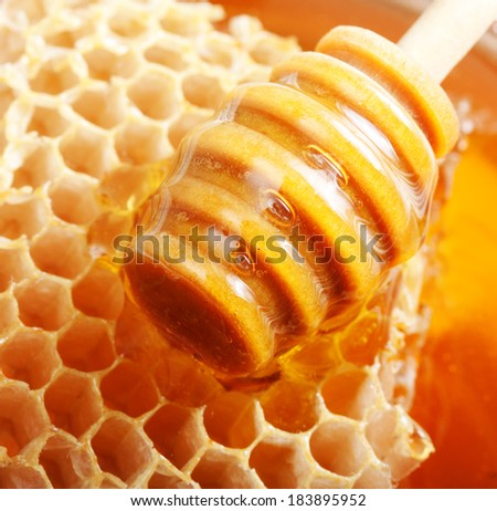 Wooden dipper, honey and honeycomb isolated on white background.