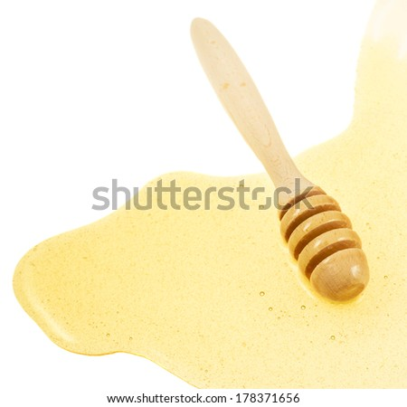 Wooden dipper in a spilled puddle of honey over white background - stock photo
