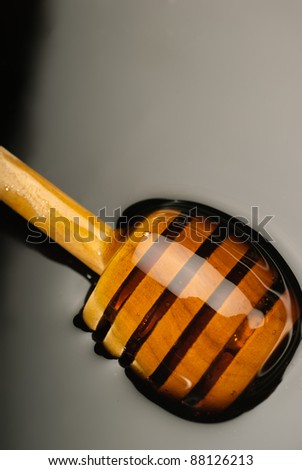 Wooden dipper in very smooth golden honey - stock photo