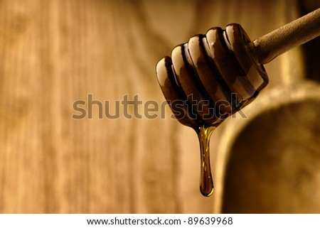 Wooden dipper with golden honey surrounded by wood - stock photo