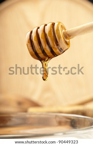 Wooden dipper with honey soft lighting - stock photo