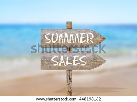 Wooden direction sign with summer sales - stock photo
