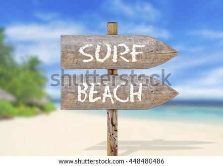 Wooden direction sign with surf beach - stock photo