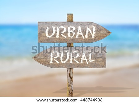 Wooden direction sign with urban and rural - stock photo