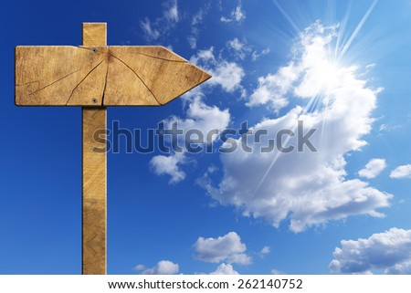 Wooden Directional Sign on Blue Sky. Wooden directional sign with one empty arrow on a blue sky with clouds and sun rays - stock photo