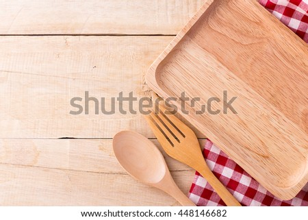 wooden dish ,fork and spoon white red tablecloth on wooden background - stock photo