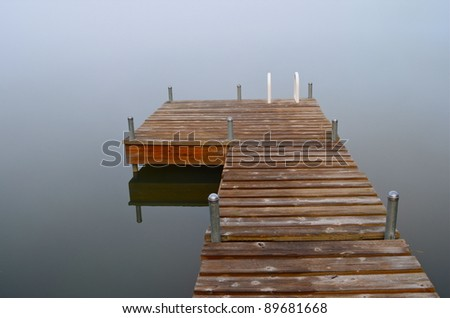 wooden dock on foggy misty water - stock photo