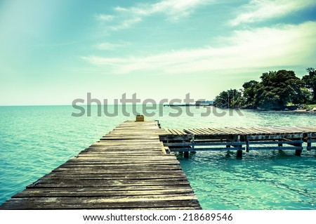 wooden dock pier overlooking sea in livingston guatemala color toned - stock photo