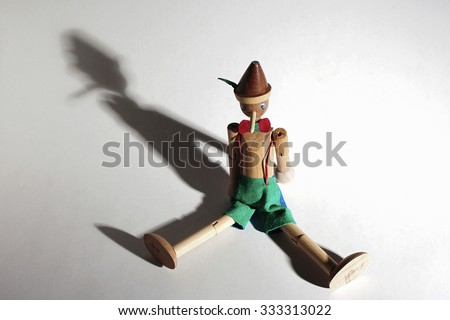 Wooden doll of Pinocchio liar with big nose. Dramatic lighting and shadows - stock photo