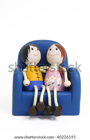wooden dolls sitting on chair