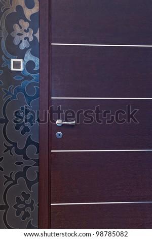 Wooden door and decorative wallpaper - stock photo