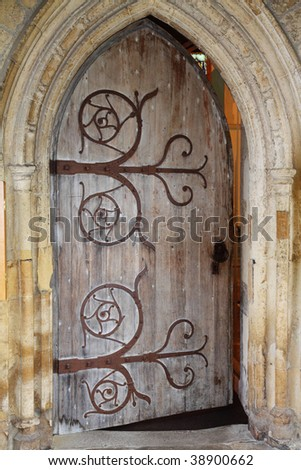 Wooden door and stone arch to a Medieval English Abbey - stock photo