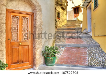 Wooden door at the entrance to small house on narrow cobbled street in town of Ventimiglia in Liguria, Italy. - stock photo