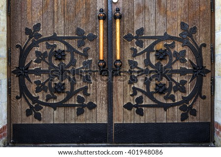 Wooden door of an old Christian church with wrought iron ornaments. As a background for design - stock photo