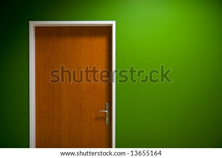 Wooden door on green wall background