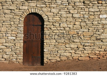 Wooden Door Stone Wall - stock photo