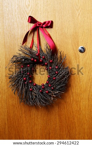 wooden door with a Christmas wreath and peephole - stock photo