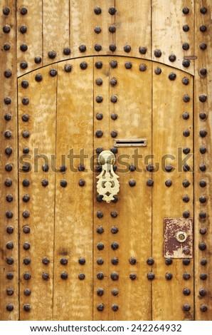 Wooden door with arab style doorknob in Marrakech, Morocco - stock photo