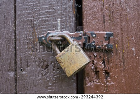Wooden door with the old iron padlock - stock photo