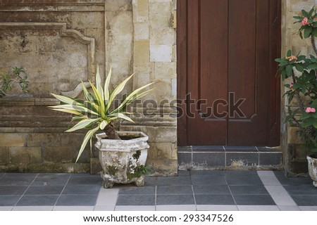 Wooden doors, stone wall and potted plant on the old Asian street, Bali, Indonesia - stock photo