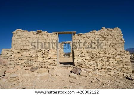 wooden doorway of limestone ruins in terlingua ghost town texas  - stock photo
