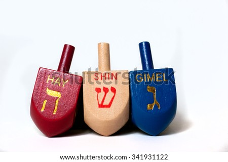 Wooden dreidels in red, wood and blue. - stock photo