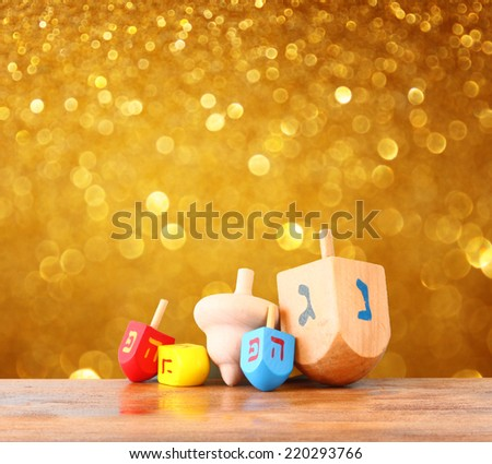 wooden dreidels (spinning top) for hanukkah jewish holiday over glitter gold background - stock photo