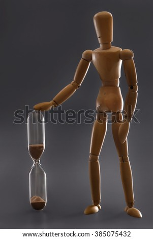 Wooden dummy touching hourglass on gray background. Timing or deadline concept - stock photo